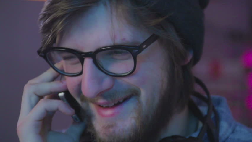 Close-up young male in glasses talking over phone smiling laughs