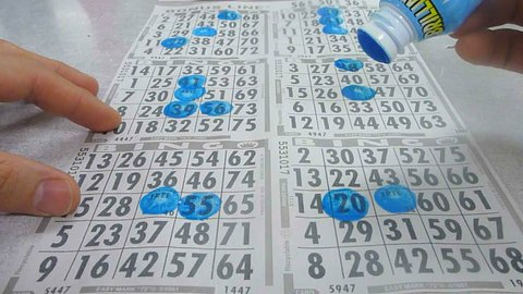 Time lapse of person stamping bingo cards.