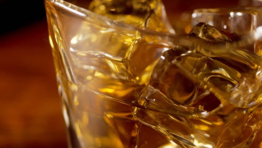 Pouring scotch whiskey over ice, close up tracking shot