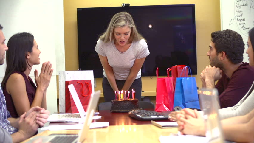 Group of office workers presenting colleague with a birthday cake with candles which she blows out in slow motion