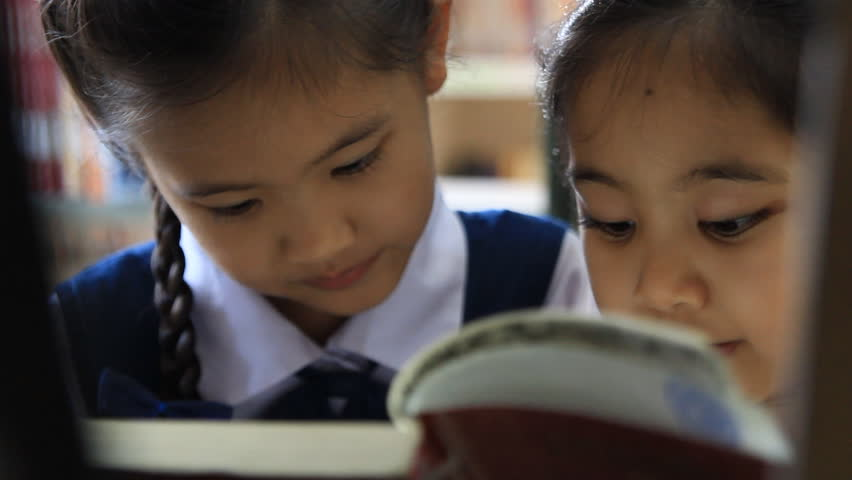 Little Asian students wearing uniforms and reading book in library
