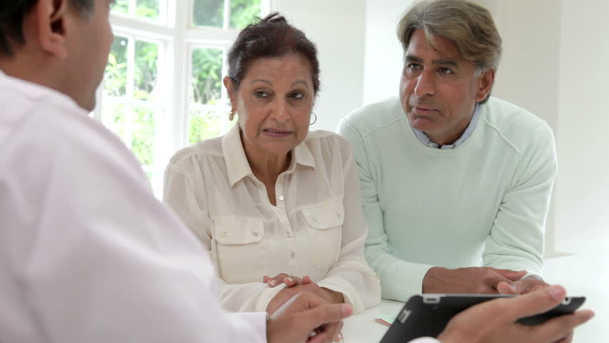 Senior Asian Indian couple discussing document with financial advisor before signing and shaking hands.Shot on Canon 5d Mk2 with a frame rate of 25fps