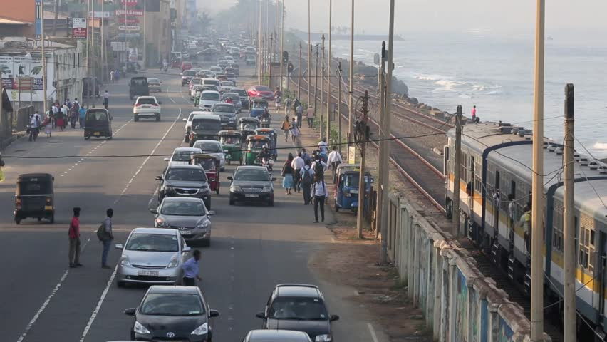 COLOMBO, SRI LANKA - MAR 17: Early morning rush hour vehicle traffic and commuter train along the city waterfront on March 17, 2014 in Colombo, Sri Lanka
