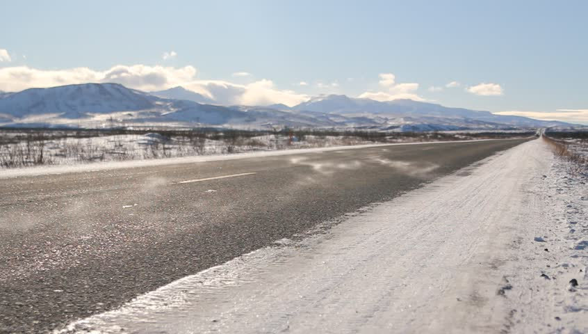 Roads Alaska Snow. Snowy mountain peaks and expansive flatland in Alaska. Features beautiful, cloudy skies, wind moving snow and a road.