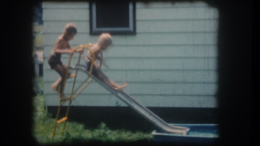 UNITED STATES - CIRCA 1950s: Old home movie film: Children playing at slide and water pool