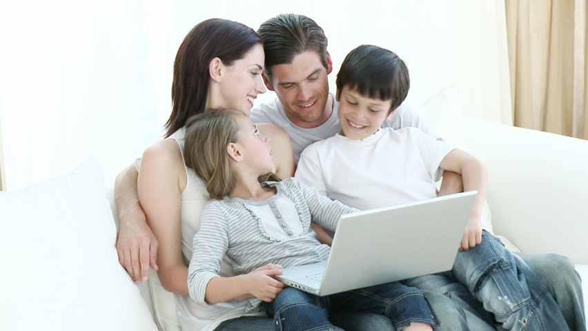 1c0eb7843a3 Happy young family using a laptop on a sofa at home. Footage in high  definition. Computer generation