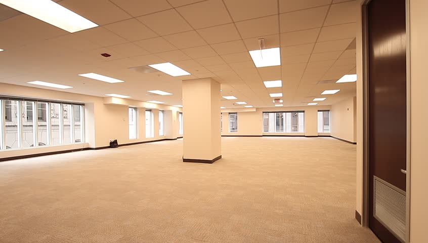 office cubicle job empty. The empty space to a future office with massive windows that lay on the outside of the room. There is a pillar directly in the center of the room.
