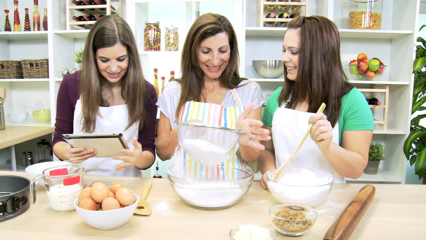 Teenage Caucasian girls home kitchen counter having baking lesson with mom  using wireless tablet recipe. Caucasian Family Females Working Together Home Kitchen Counter