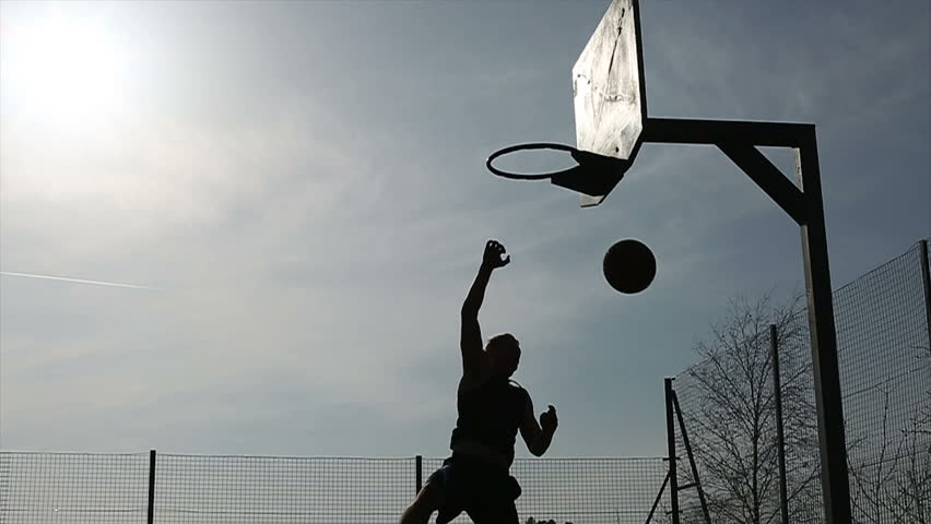 Basketball player silhouette making a fancy 180 degree slam dunk #5982569