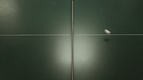 A game of table tennis or ping pong viewed from above as the ball goes back and forth