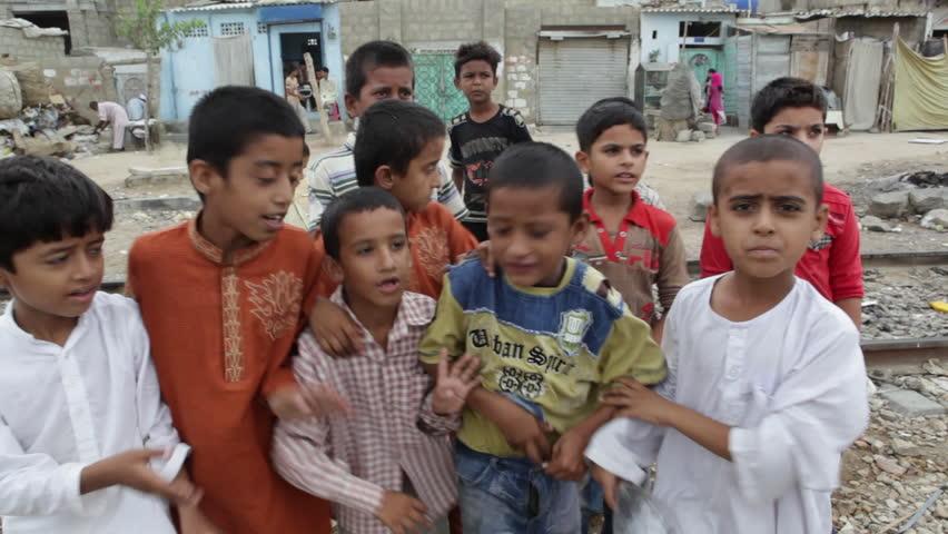 "KARACHI, PAKISTAN - JULY 28, 2013: A group of boys mug for the camera, yelling ""Pakistan!"""
