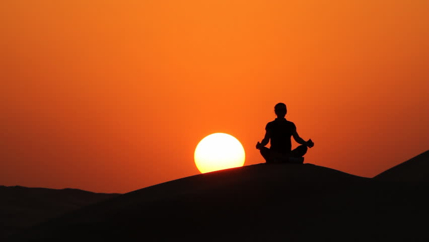 woman sitting in lotus position at amazing sunset