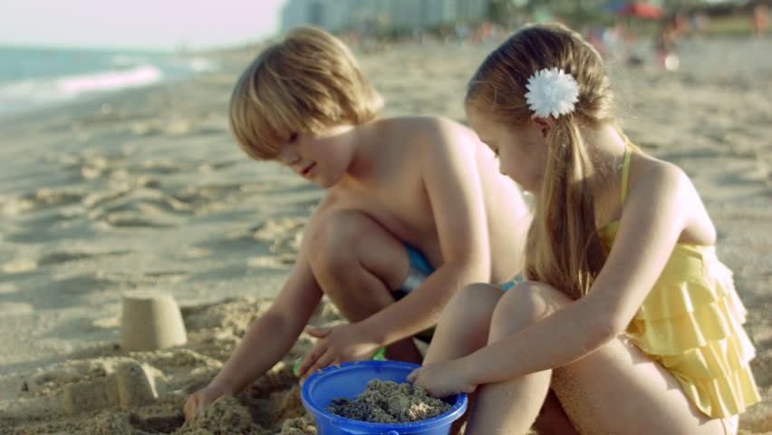 Closeup Of Boy And Girl Hard At Work, Building Castles In The Sand
