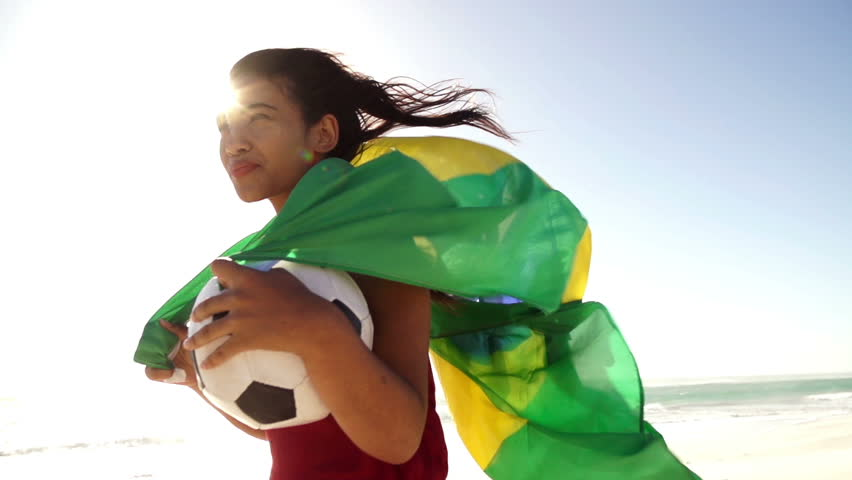 Brazilian soccer fan with ball and waving flag in slow motion