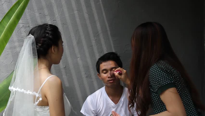 Makeup artist apply makeup to an attractive young groom   Shutterstock HD Video #6053249