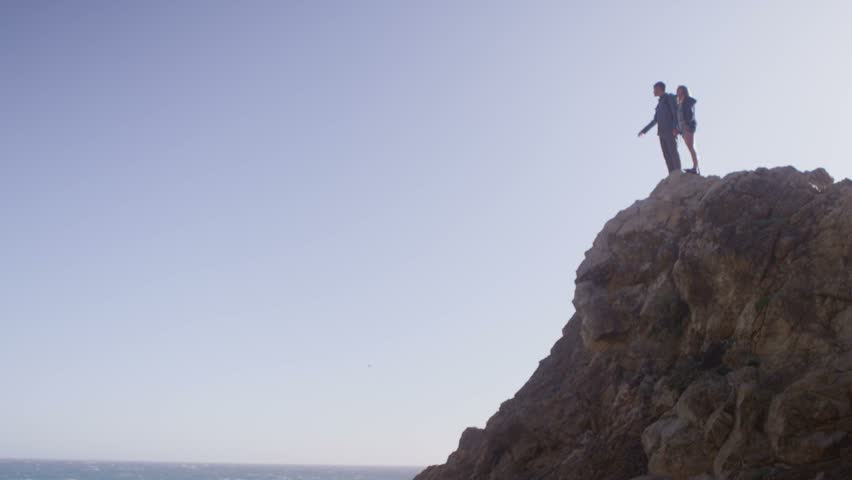 Wide view of a couple standing atop a sea cliff. | Shutterstock HD Video #6058238