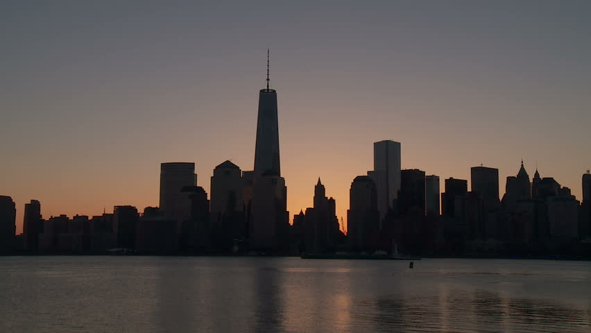 (Timelapse) The sun rises behind the Freedom Tower and the buildings of the World Trade Center complex, as morning twilight transitions to day over the skyline of lower Manhattan in New York City.