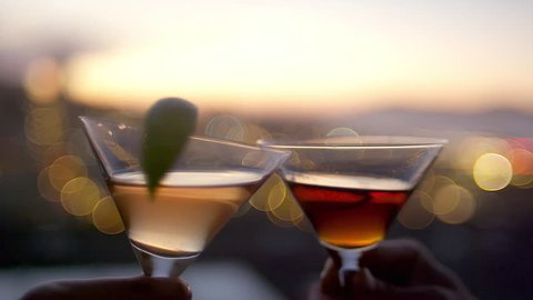 Close up of two cocktail glasses toasting on rooftop at dusk