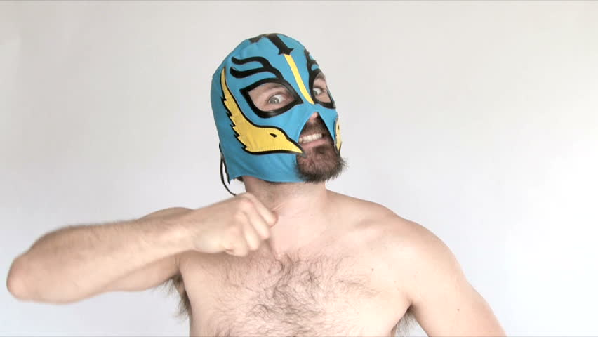 Model released man in studio wearing blue lucha libre mask challenges viewer.