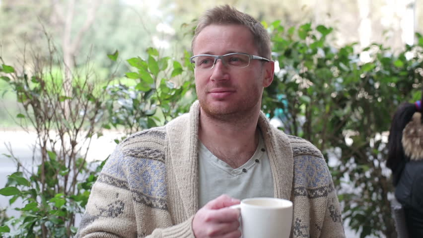Young man drinking coffee in the restaurant, outdoors  | Shutterstock HD Video #6101999