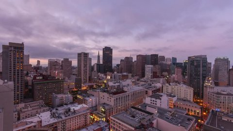 Day to night time-lapse of the San Francisco skyline showcasing the city lights as the sun sets.