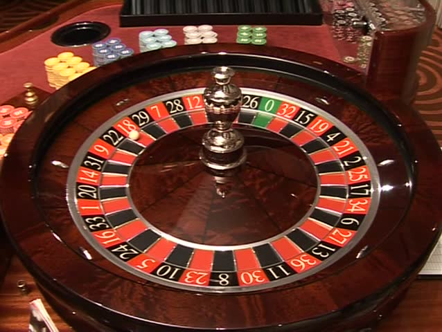 Turning roulette wheel in casino.