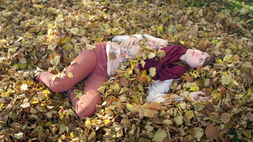 A young woman lays in a pile of leaves in the park and looks to the sky lost in thought | Shutterstock HD Video #6119453