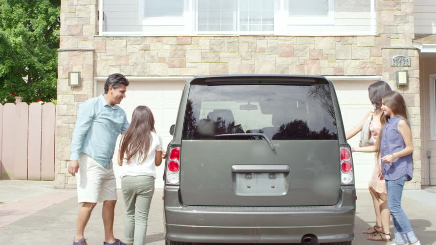 A family of four gets into a car which is sitting in the driveway of their house