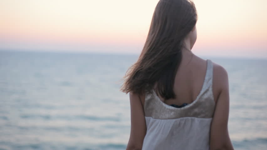 Sad happy girl prays at sunset by the sea