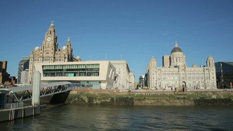 Tracking clip of Pierhead buildings taken from moving ferry as it approaches Liverpool waterfront skyline, England