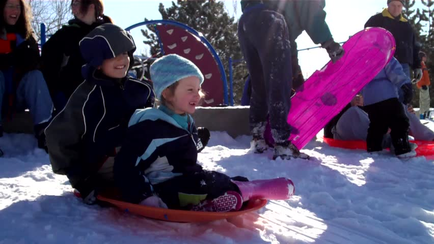 cute little girl slides down a huge snow-covered hill on a sledding saucer