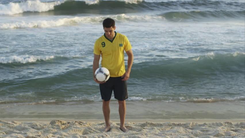WS A young man practices his soccer skills on Ipanema Beach / Rio de Janeiro, Brazil