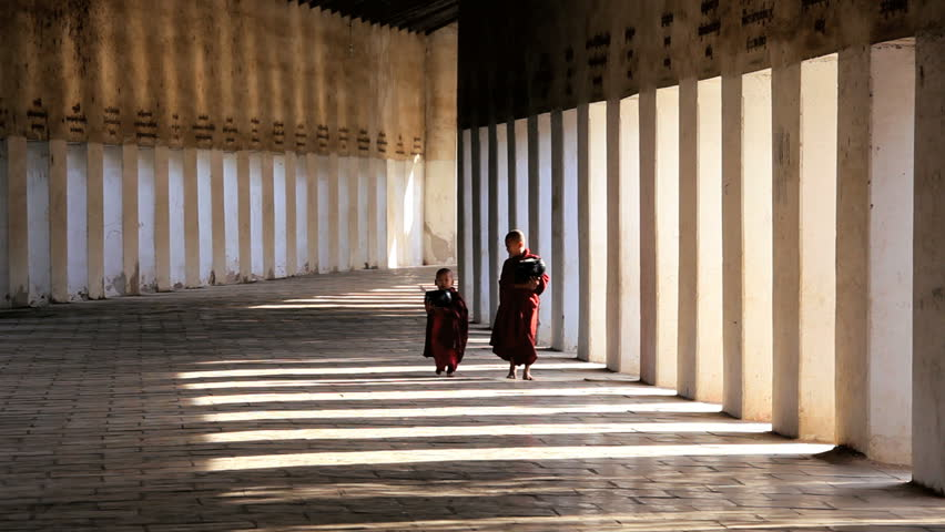 Burma - February 2013: Novice Monks dressed in traditional clothes in Walkway to Shwezigon Pagoda, Bagan, Asia