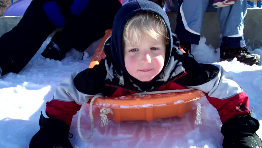 action clip of cute little boy riding down a steep hill on a toboggan