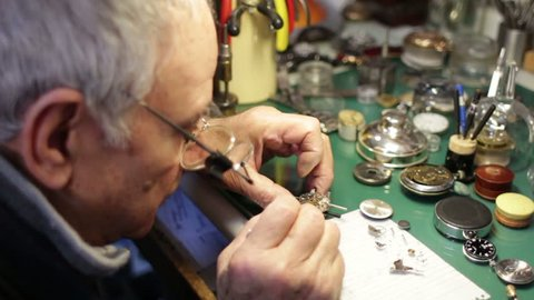 watchmaker disassembles a wristwatch for repair