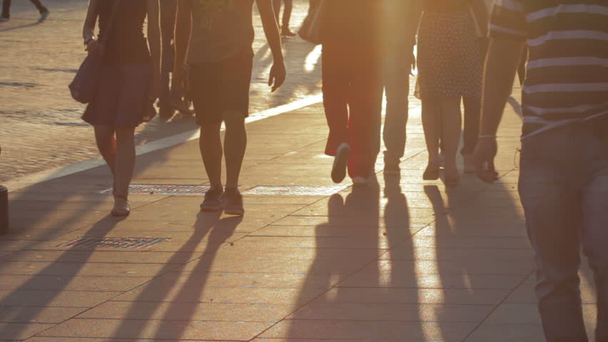 People walking at sunset, long shadows of people in silhouette anonymous