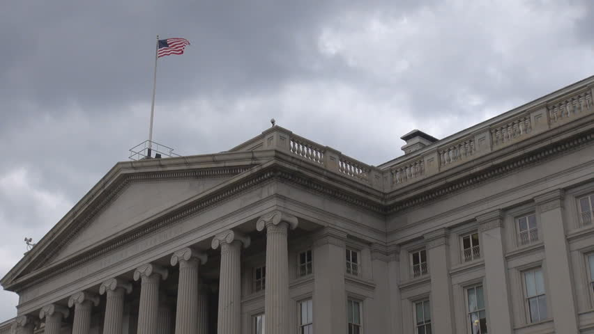 The United States Treasury Department building, the facade with flag and cloudy sky by day in Washington DC, USA
