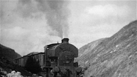 Cranford, Northamptonshire, UK - August, 1964: Digital copy of a grainy old black and white film of a steam railway locomotive named Cranford hauling a train of mineral wagons in an ironstone quarry.