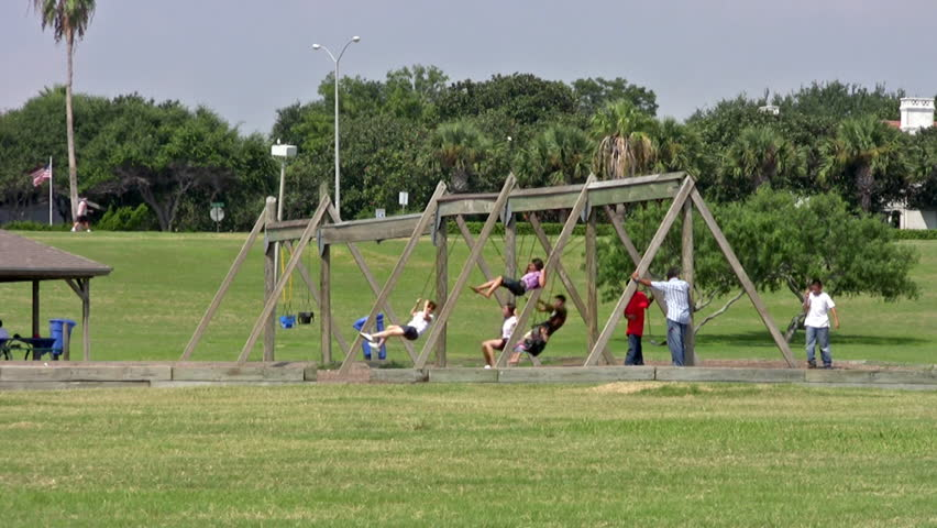 Video of playground chain swings in a kids or children park. Rubber seat moving in the wind. Kids activity and recreation.