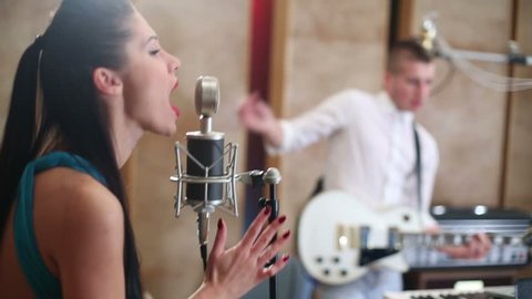 Girl with long hair sings to microphone and man plays guitar in Recording Studio
