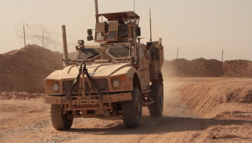 US marine MRAPs driving past camera on a dusty road in the Middle East