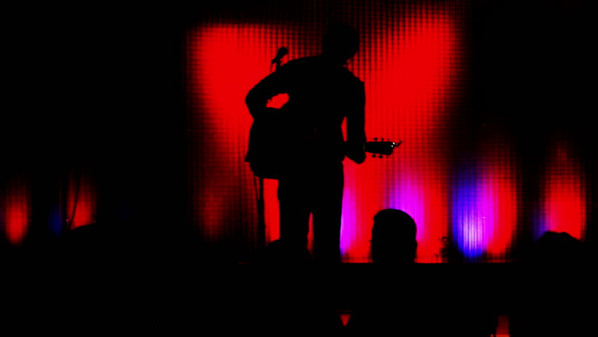 Man Playing and Performing with a Guitar Silhouette