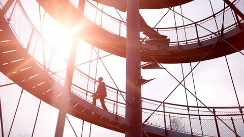 businessman walking on stairway. progress upwards growth. successful business man. male silhouette. futuristic architecture. sunset dusk.