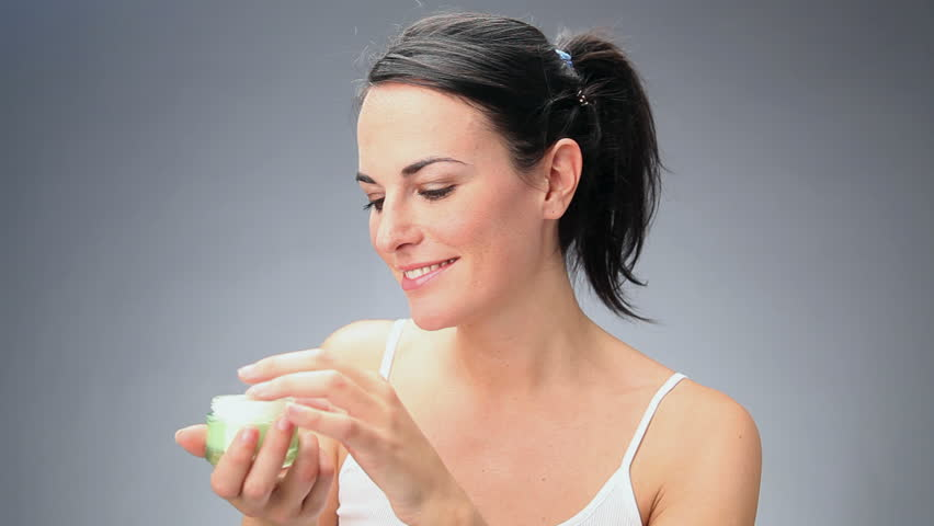 Female beauty, happy mid adult woman putting cream on face skin and smiling, looking at camera