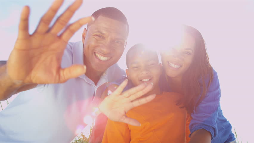 African American Parents Child Outdoors Photo Messaging - Portrait happy young African American family group casual vacation clothes outdoors together messaging friends social media sun lens flare
