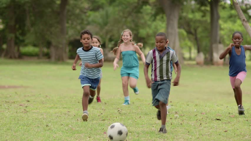 Young people, happy friends and ball sport, kids and children, multiethnic group of  boys and girls playing european football, american soccer in city park. Summer camp fun. Slow motion.