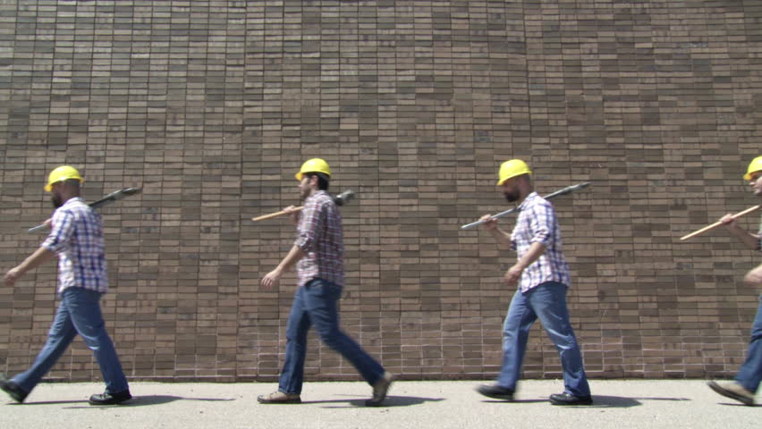 Two contractors with a sledgehammer and an adjustable wrench walk endlessly past the same brick wall.  Locked off wide shot.  Looping clip.