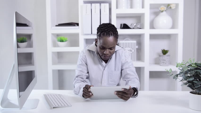 home office multitasking. delighful office african american man working with tablet computer in home office  hd stock  video clip throughout home office multitasking t