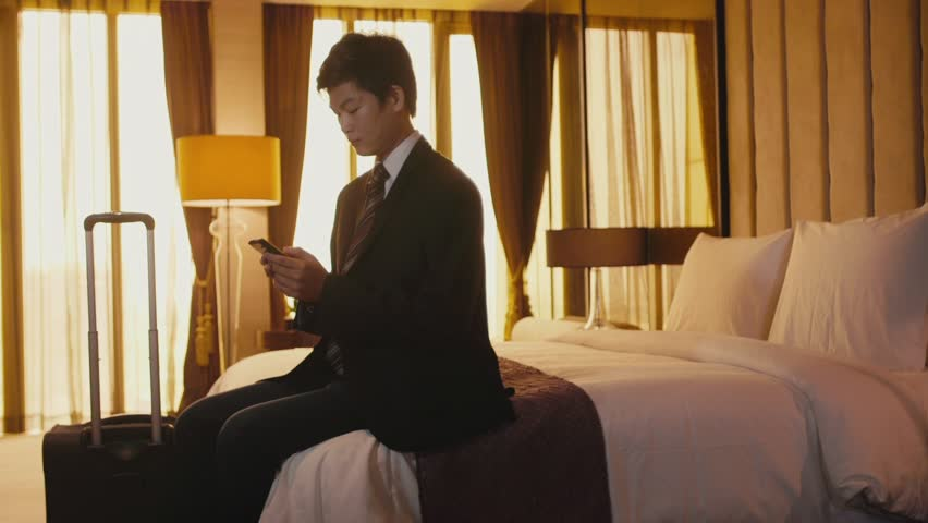 Business travel, people traveling, working in hotel room, manager. Asian businessman, chinese man at work, using smart-phone, mobile phone, telephone for email, internet, facebook. 13of21
