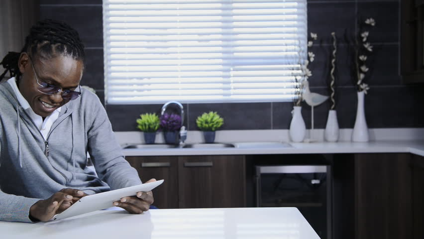 African American Man Using Tablet Computer In Modern Kitchen Stock